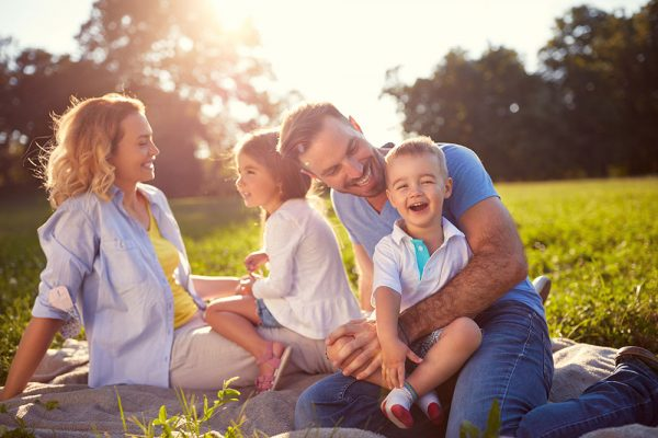 A family of four with a young son and daughter with ADHD sit in the grass and play.