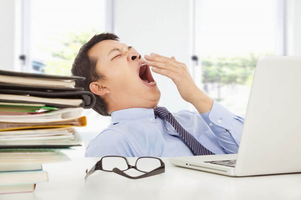 A man with ADHD struggles with daytime tiredness, yawning at his desk.