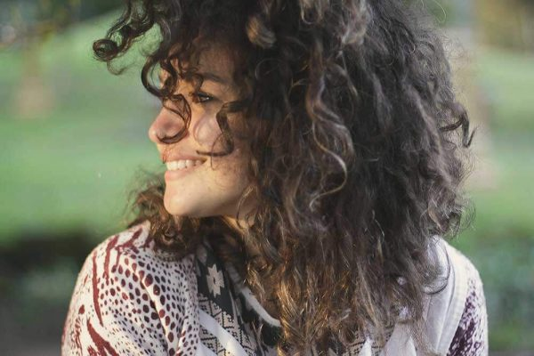A woman with curly hair and ADHD is outside and smiling because she has slept well.