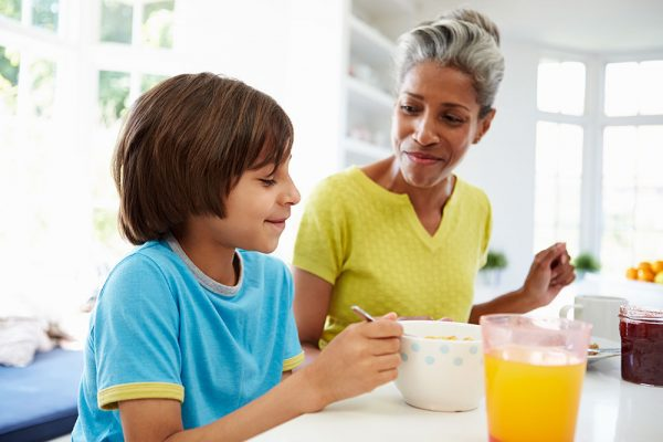 A woman and her son eat breakfast together. They're making healthy choices to control their sleep apnea weight.