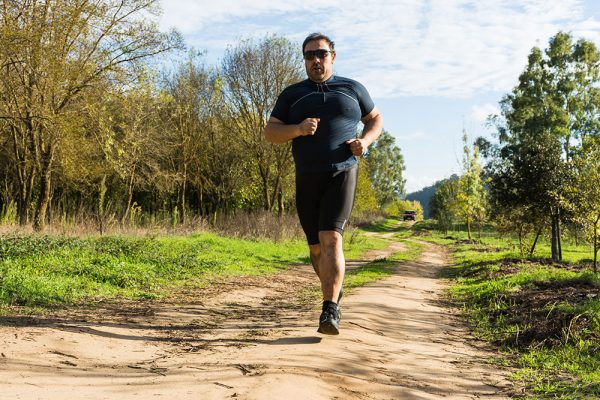 A man is running on a dirt path to lose sleep apnea weight.