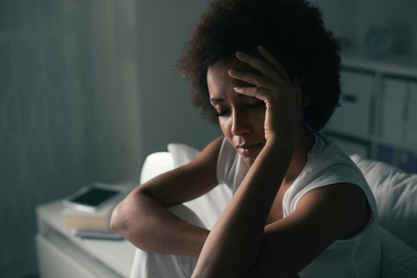 woman with afro sitting in bed unable to sleep