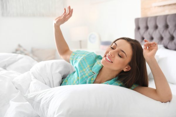 woman laying in bed smiling
