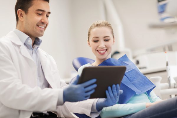 dentist showing a screen to a female patient in the chair as they both smile
